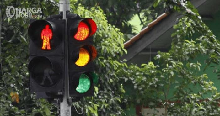 Gambar ini menunjukkan lampu lalu luntas dengan 3 warna dan gambar orang