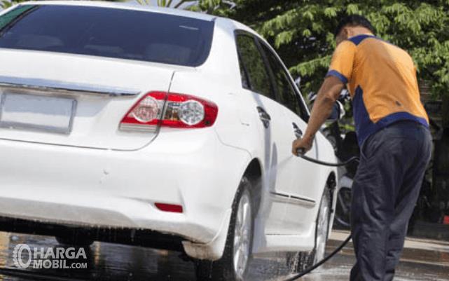 Gambar ini menunjukkan seorang pria sedang menyiram mobil warna putih