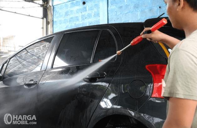 Gambar ini menunjukkan seorang pria sedang menyemprot mobil dengan warna hitam