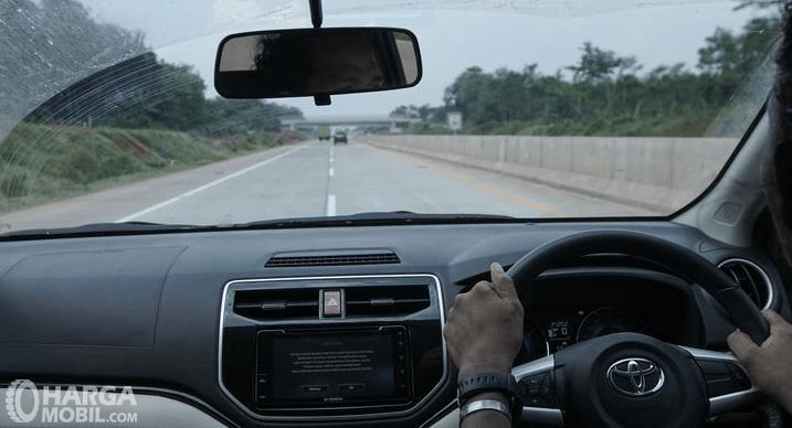 Gambar ini menunjukkan jalan tol dilihat dari dalam kendaraan