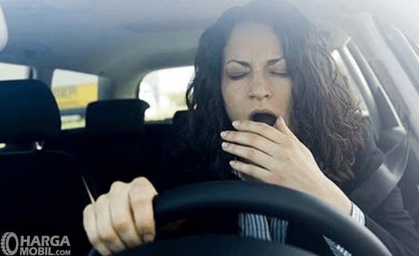 Gambar ini menunjukkan seorang wanita sedang menguap di dalam mobil