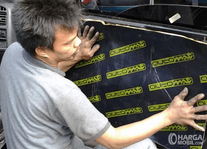 Gambar ini menunjukkan seorang pria memasang peredam pada pintu mobil