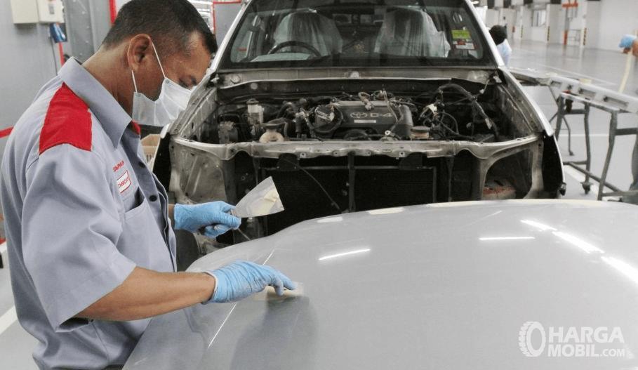 Gambar ini menunjukkan seorang montir sedang memegang kain ditempelkan pada bodi mobil