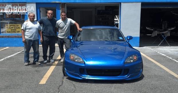 Gambar ini menunjukkan 3 orang sedang berdiri di samping mobil warna biru
