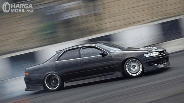 Gambar ini menunjukkan mobil BMW 323i E36  warna hitam sedang melakukan drifting