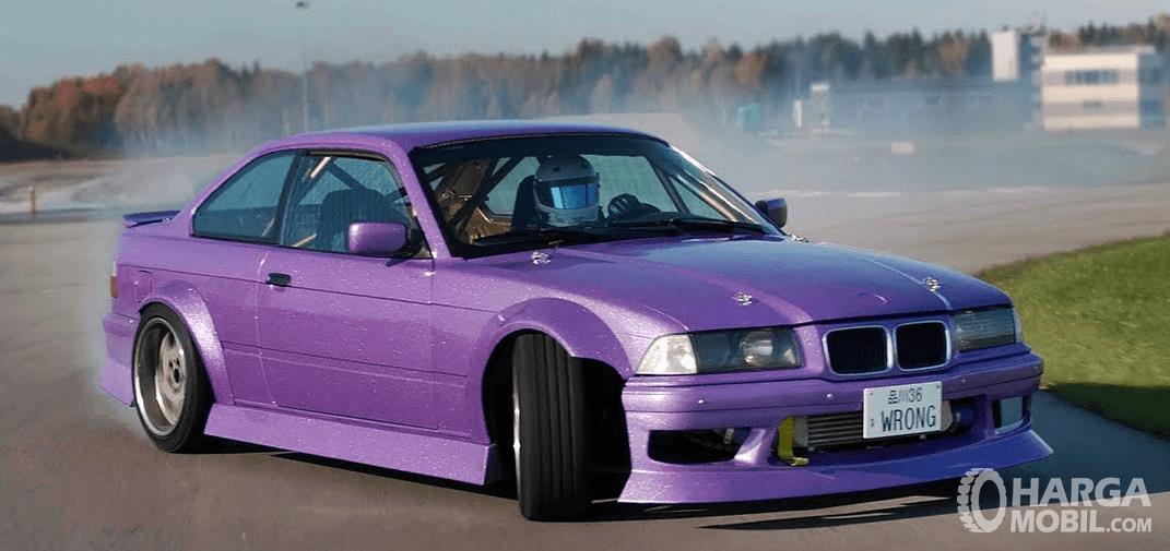 Gambar ini menunjukkan mobil BMW 323i E36  warna ungu sedang melakukan drifting