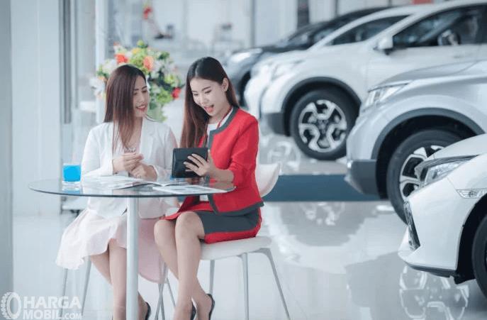 Gambar ini menunjukkan 2 orang wanita sedang duduk melihat ponsel