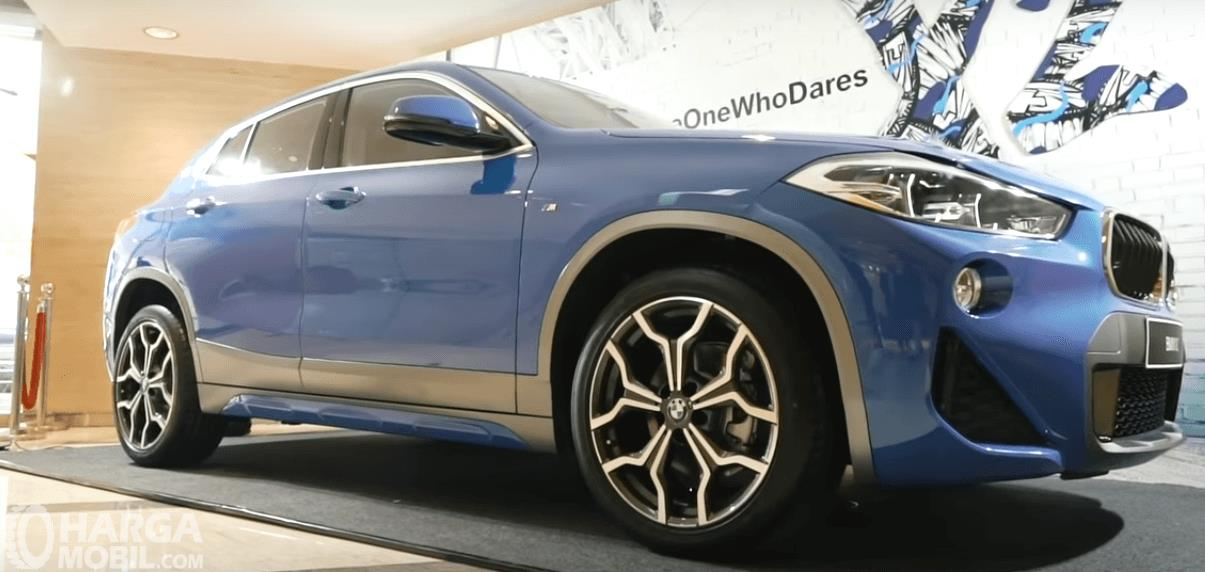 Gambar ini menunjukkan mobil BMW X2 warna biru tampak depan dan samping kanan