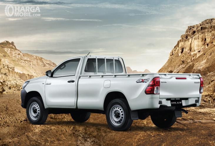Gambar ini menunjukkan mobil Toyota Hilux S-Cab warna putih tampak belakang dan kiri