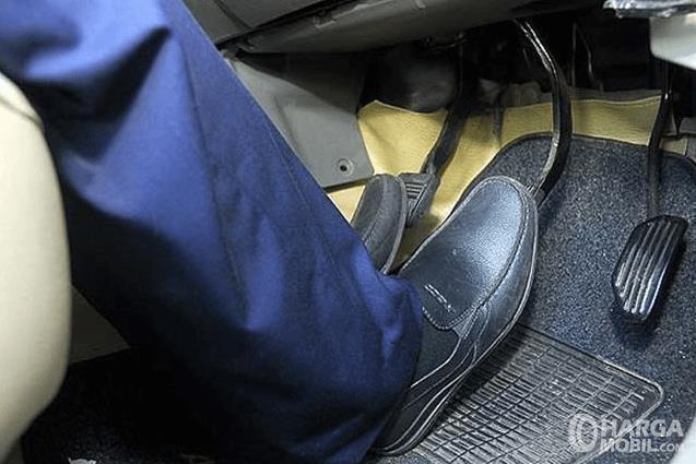 Gambar ini menunjukkan kaki sedang menginjak pedal rem dan kopling
