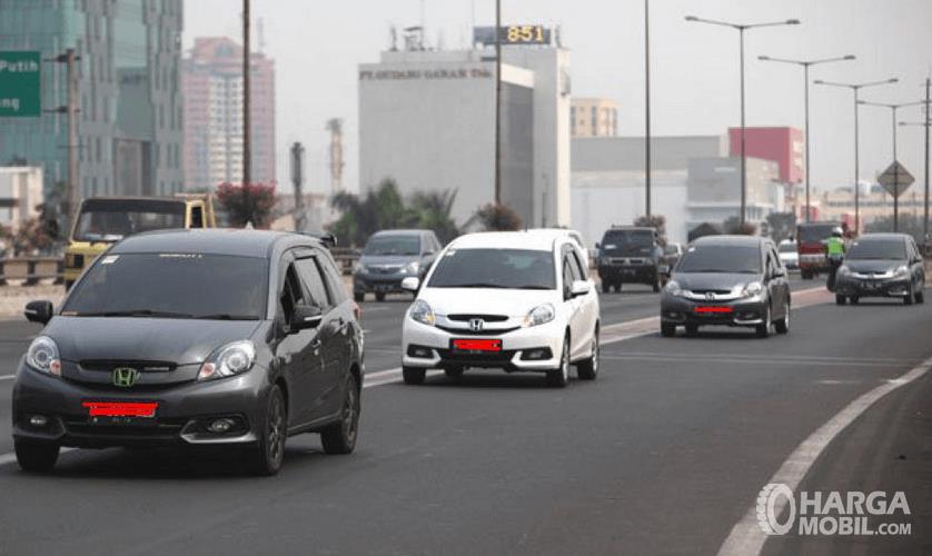 Gambar ini menunjukkan beberapa mobil sedang melaju di jalan raya