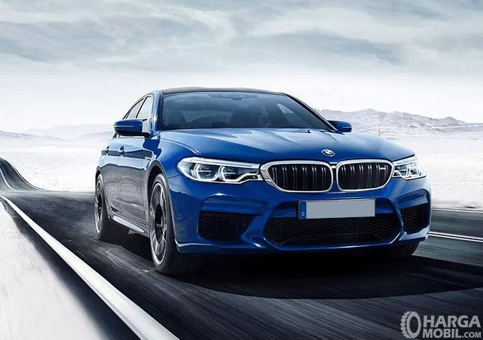 Gambar ini menunjukkan mobil BMW M5 warna biru tampak depan dan samping kanan
