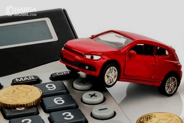Gambar ini menunjukkan miniatur mobil berada di atas kalkulator
