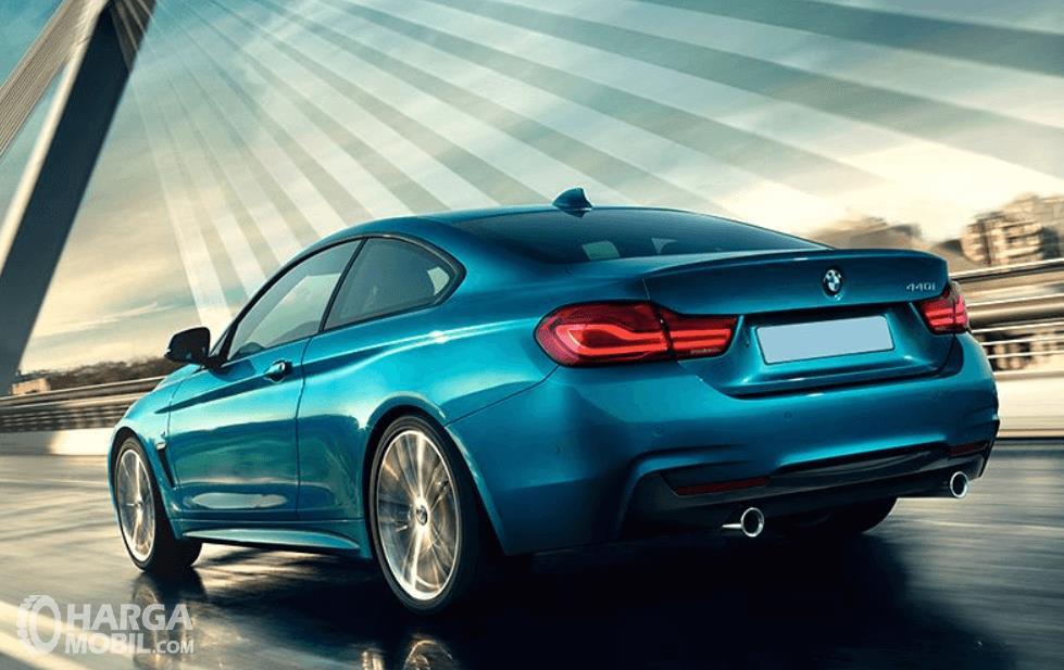 Gambar ini menunjukkan mobil BMW M4 warna biru tampak belakang