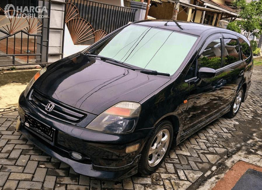 Gambar ini menunjukkan mobil Honda Stream warna hitam tampak samping kii dan depan