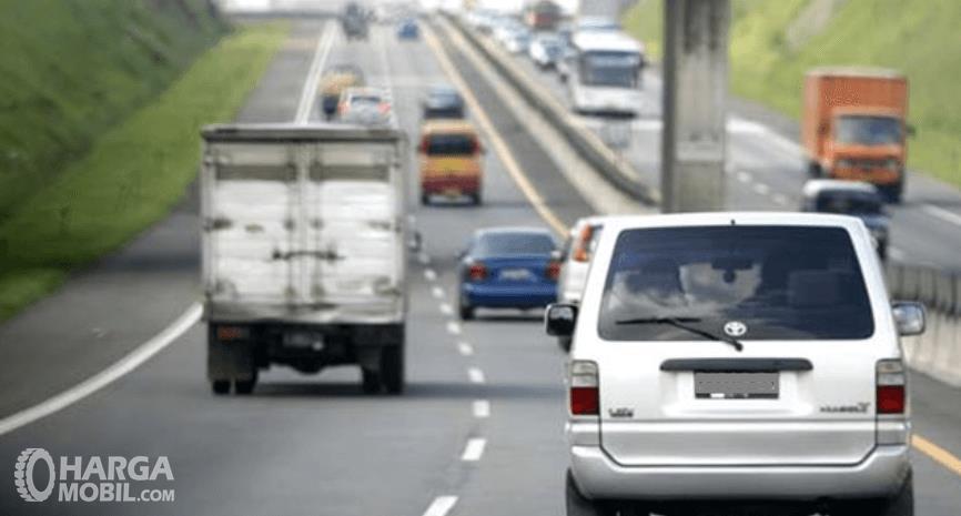 Gambar ini menunjukkan banyak mobil berbagai enis melaju di jalan tol