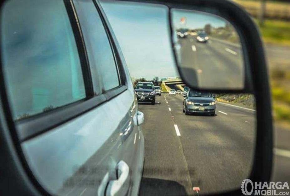 Gambar ini menunjukkan spion mobil tampak ada beberapa kendaraan terlihat