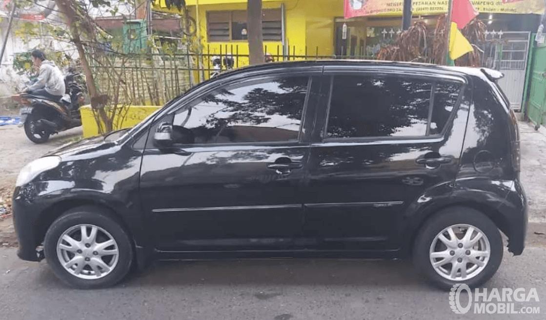 Gambar ini menunjukkan bagian samping mobil Daihatsu Sirion 2007 hitam
