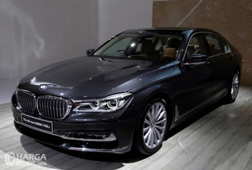Gambar ini menunjukkan mobil BMW 740Li warna hitam tampak depan dan samping kiri