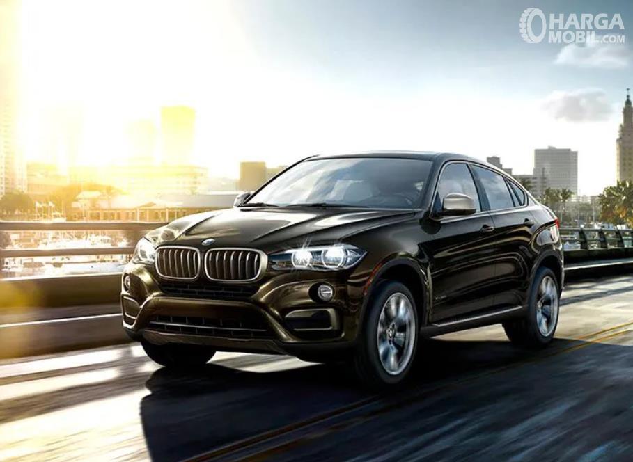 Gambar ini menunjukkan mobil BMW X6 melaju di jalan  tampak depan dan samping kiri
