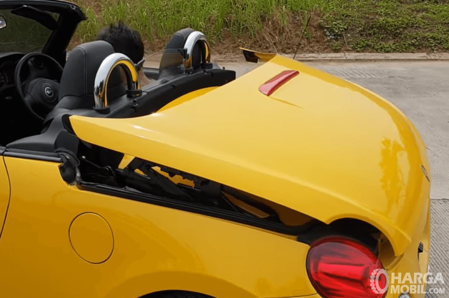 Gambar ini menunjukkan mobil  Daihatsu Copen 2003 dengan kap belakang akan membuka
