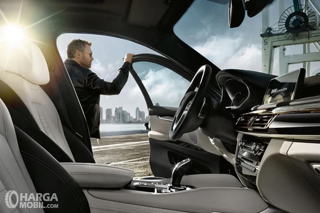 Gambar ini menunjukkan seorang pria memegang pintu mobil dan tampak interior BMW X6