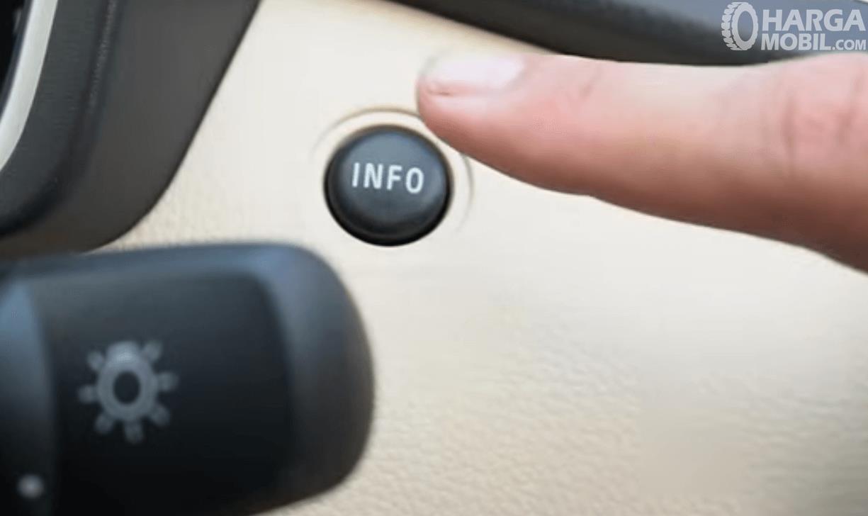 Gambar ini menunjukkan tombol INFO dan sebuah jari akan menekannya