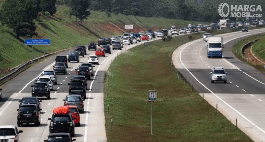 Gambar ini menunjukkan banyak mobil sedang melewati jalan tol