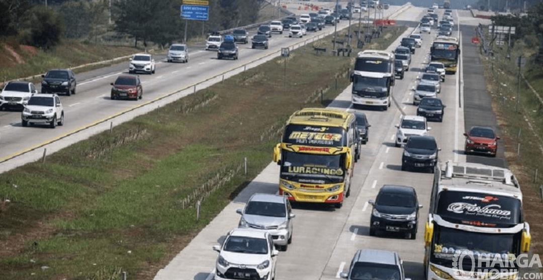 Gambar ini menunjukkan jalan tol dengan banyak kendaraan yang barvariasi