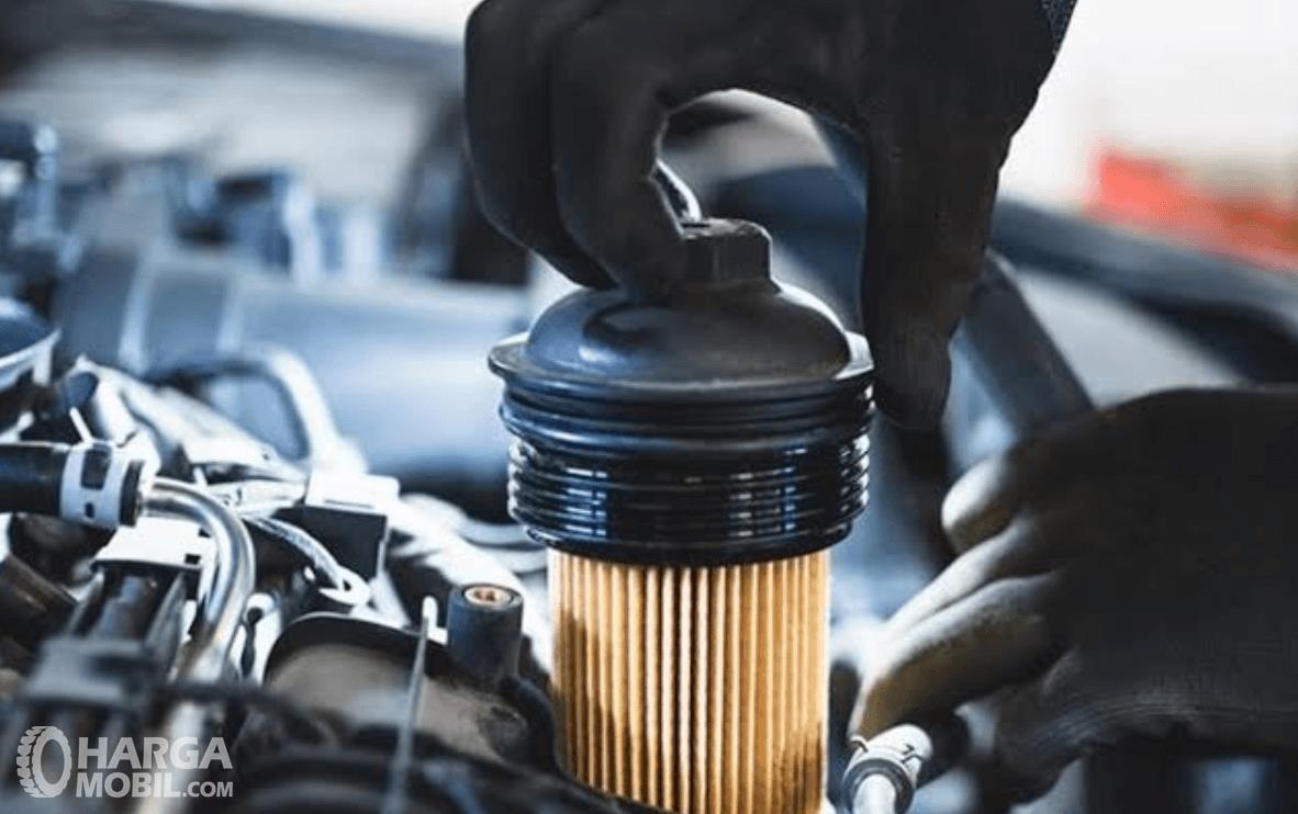 Gamabr ini menunjukkan sebuah tangan menarik filter oli di mesin mobil