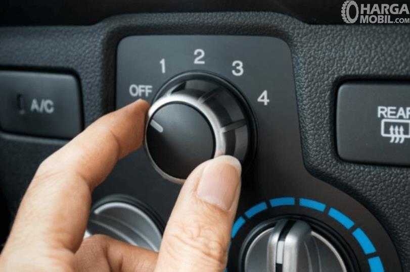 Gambar ini menunjukkan sebuah tangan sedang memutar knob AC mobil