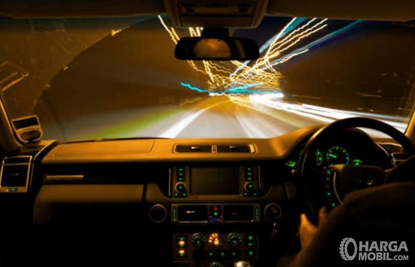 Gambar ini menunjukkan interior mobil dalam kondisi malam hari