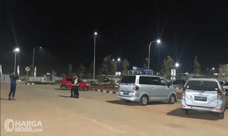 Gambar ini menunjukkan 2 mobil dan ada 2 orang di belakangnya sedang berbincang