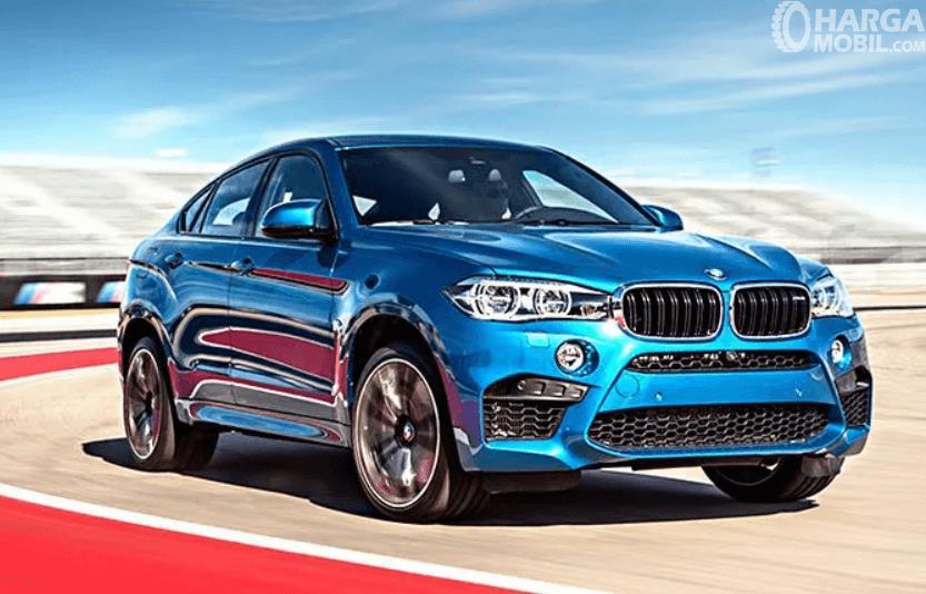 Gambar ini menunjukkan mobil BMW X6 M warna biru tampak depan dan samping kanan