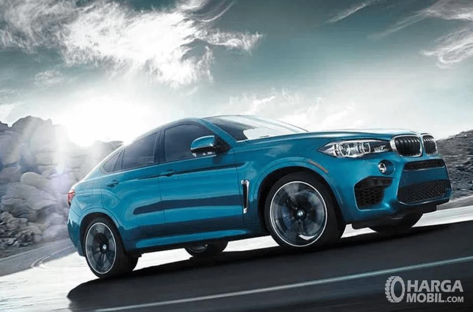 Gambar ini menunjukkan mobil BMW X6 M tampak samping sedang melaju di tanjakan