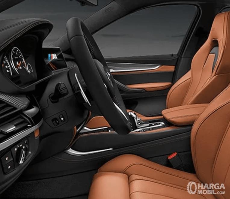 Gambar ini menunjukkan interior mobil BMW X6 M tampak jok depan dan dashboard serta kemudi