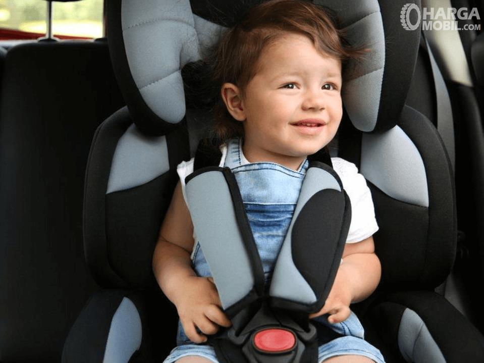 Gambar ini menunjukkan seorang anak duduk di kursi khusus di dalam mobil