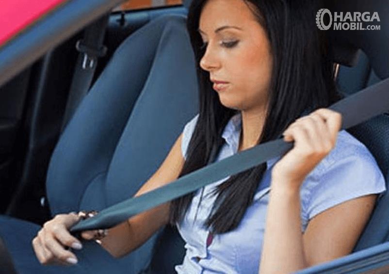 Gambar ini menunjukkan seorang wanita sedang memasang seat belt pada mobil