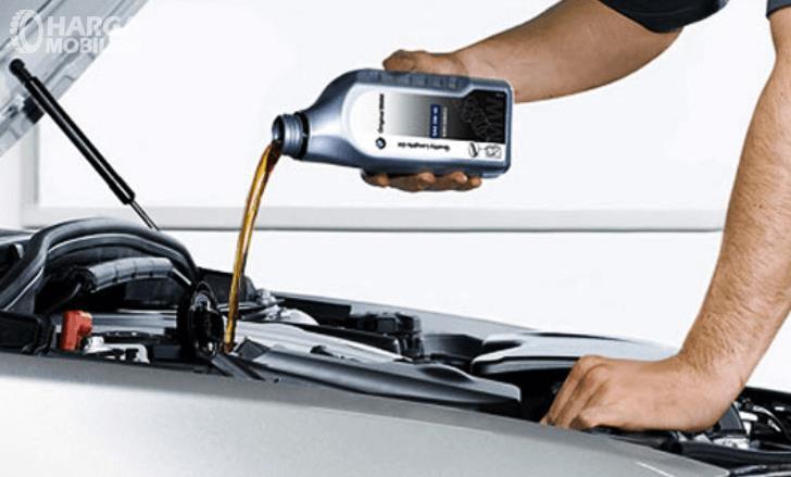 Gambar ini menunjukkan seseorang sedang mengisi oli pada mobil