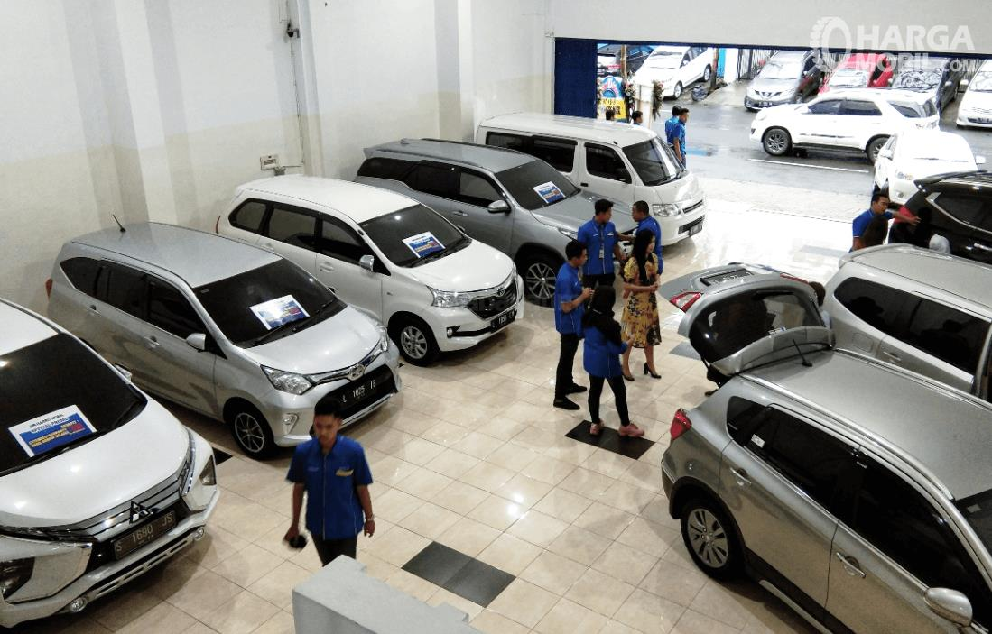 Gambar ini menunjukkan beberapa mobil dan orang dalam ruangan