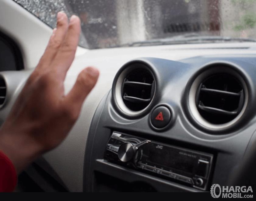 Gambar ini menunjukkan sebuah tangan berada di depan kisi-kisi AC mobil