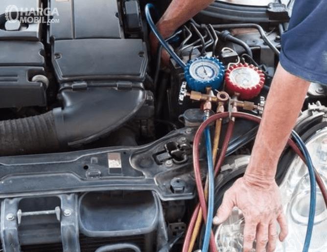 Gambar ini menunjukkan seseorang sedang melihat kondisi pada mesin mobil