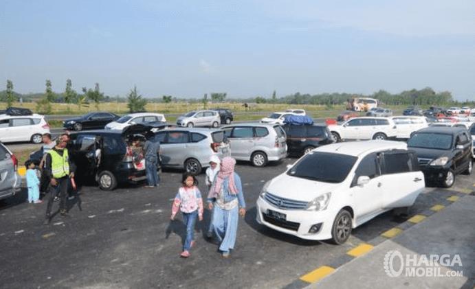 Gambar ini menunjukkan banyak orang dan mobil sedang berhenti di rest area