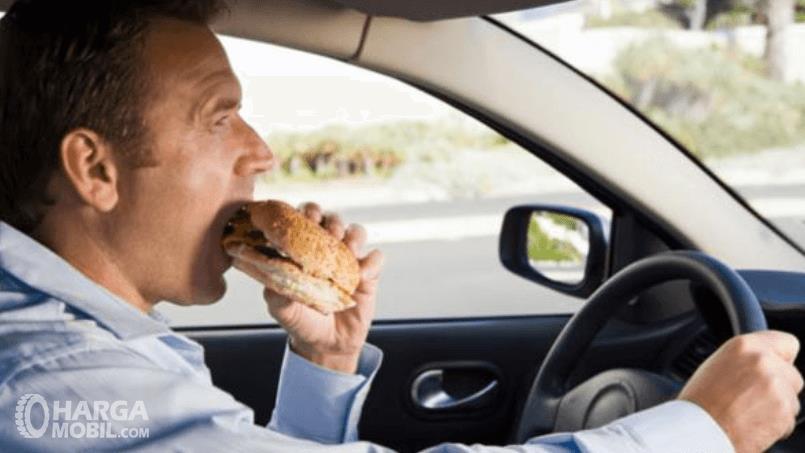 Gambar ini menunjukkan seorang pria sedang makan sambil mengemudi