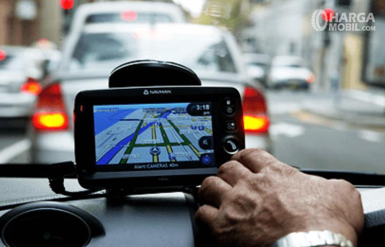 Gambar ini menunjukkan sebuah tangan sedang mengatur layar navigasi