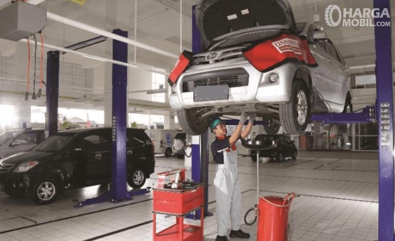 Gambar ini menunjukkan sebuah mekanik sedang memeriksa kondisi mobil