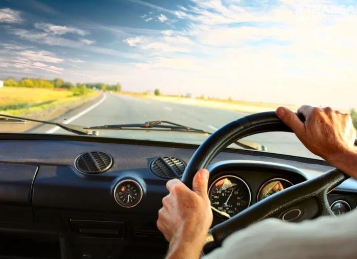 Gambar ini menunjukkan 2 buah tangan memegang kemudi mobil