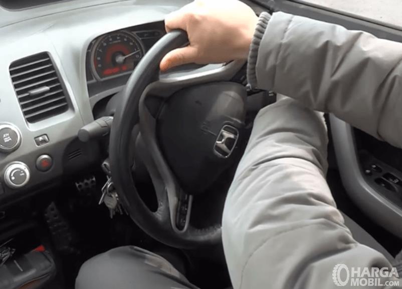 Gambar ini menunjukkan 2 buah tangan sedang memutar kemudi mobil