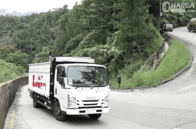 Gambar ini menunjukkan mobil truk melewati tanjakan yang menikung