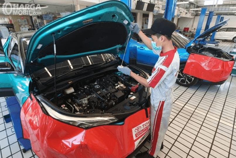 Gambar ini menunjukkan seorang mekanik di bengkel resmi memeriksa mobil hybrid